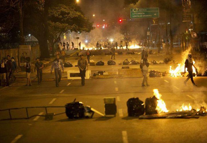 Se ven en las calles objetos que colocaron los manifestantes de la oposición y que bloquean una carretera en el barrio Altamira de Caracas, Venezuela. (Agencias)