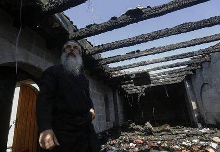 Un clérigo cristiano inspecciona los daños causados a la Iglesia de Tagbha, Israel, situada cerca del Mar de Galilea y donde la tradición sitúa el milagro de la multiplicación de los panes y los peces de Jesucristo. (EFE)