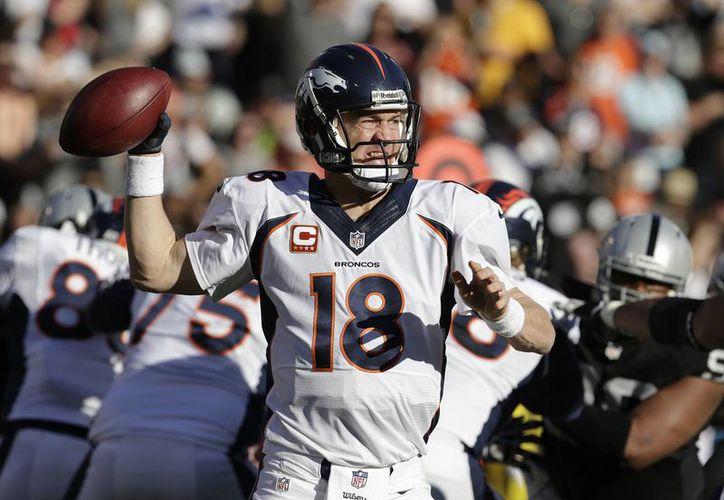El quarterback de los Broncos de Denver Peyton Manning (18) realiza un pase contra los Raiders de Oakland. (Agencias)