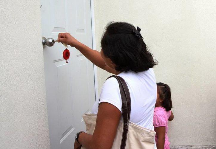 Familias beneficiadas entran a su nuevo hogar. (SIPSE)