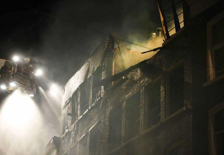 Los bomberos intentan apagar el incendio declarado en varios edificios en el centro de Leeuwarden, en Holanda. (EFE)
