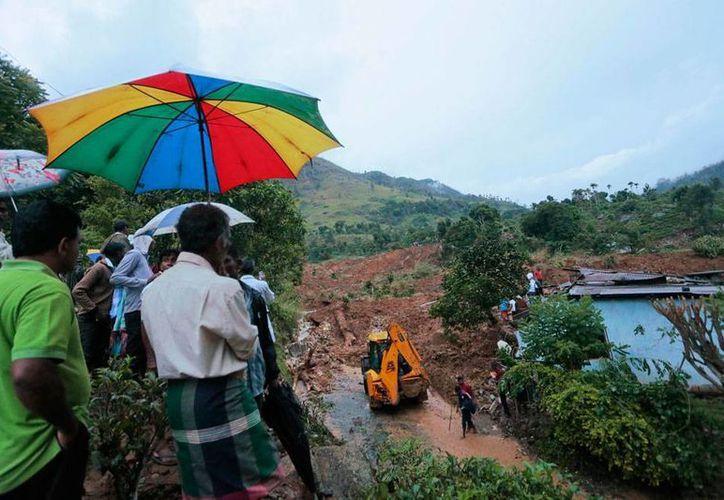 Habitantes de una zona castigada por las lluvias del monzón, en Sri Lanka, observan las labores de una pala que remueve el lodo. Al menos 10 personas  murieron y 250 están desaparecidas a causa del mal tiempo. (AP)