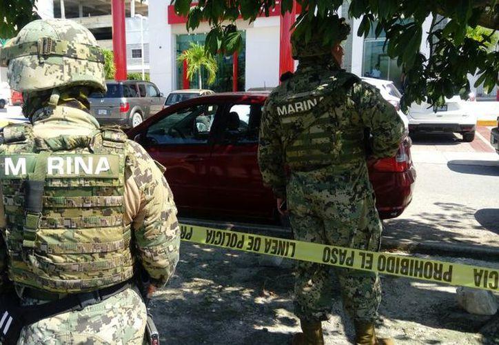 Elementos ministeriales y de la Marina acordonaron la zona sobre la avenida Xcaret, tras el atraco en la institución bancaria. (Redacción/SIPSE)