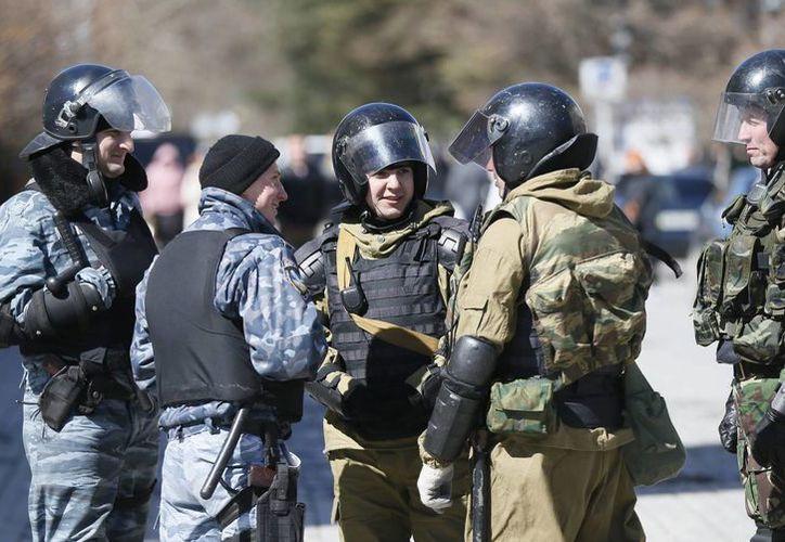 Varios militares se reúnen cerca del Parlamento, tras el referéndum en el que el 96.77 % de los votantes crimeos mostró su apoyo ayer a favor de la reunificación con Rusia, en Simferópol, en la península ucraniana de Crimea hoy. (EFE)