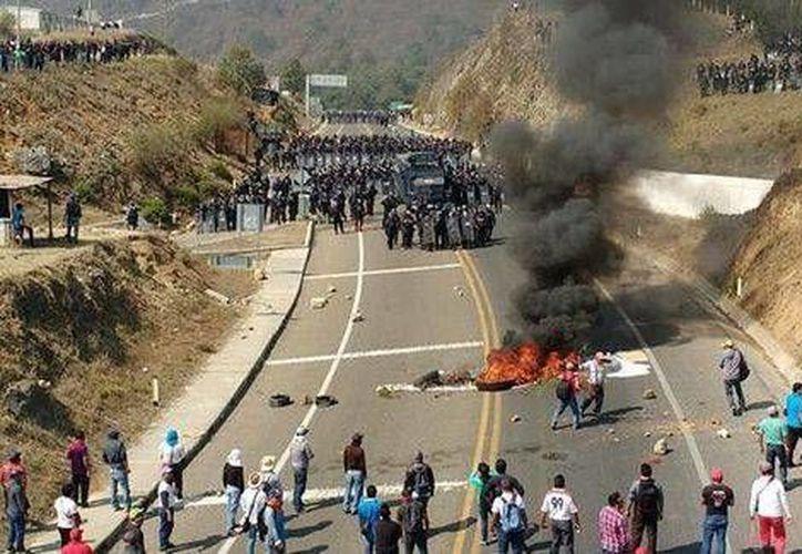 Los maestros quemaron vehículos en protesta por la detención de uno de sus compañeros. (Milenio)