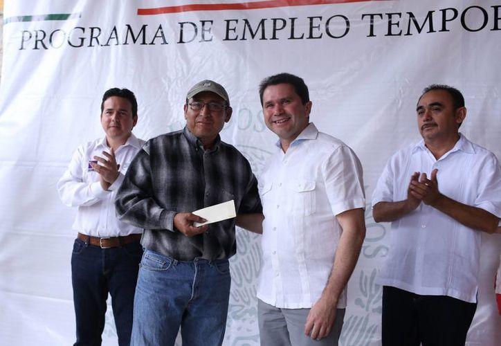 En representación del gobernador Rolando Zapata Bello, el titular de la Secretaría de Desarrollo Social (Sedesol), Mauricio Sahuí Rivero (d), inició el pago correspondiente al Programa de Empleo Temporal (PET) en Tixkokob. (Foto cortesía del Gobierno)