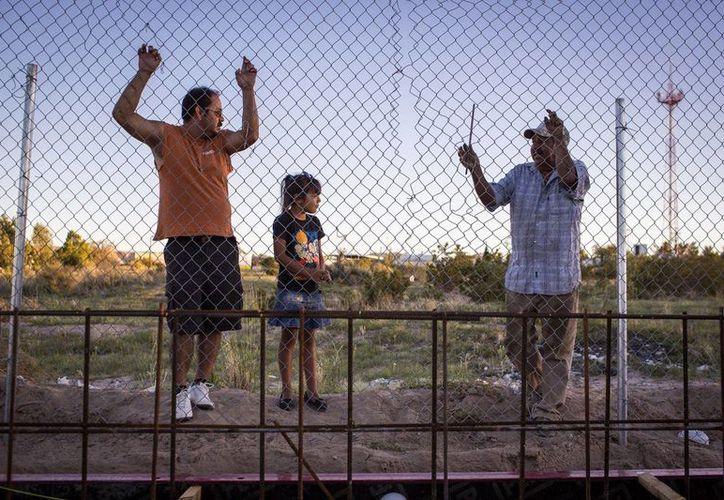 Luis, América y Rubén Maldonado observan el progreso en la construcción de los casi dos km del muro de acero reforzado que levanta EU en la localidad fronteriza de Sunland Park, Nuevo México. (EFE)