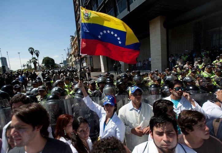 Un médico agita una bandera de Venezuela cerca de una línea de la Policía Nacional Bolivariana que bloquea una protesta para que llegue a la oficina del vicepresidente en el Día Nacional del Médico en Caracas, Venezuela. (Agencias)