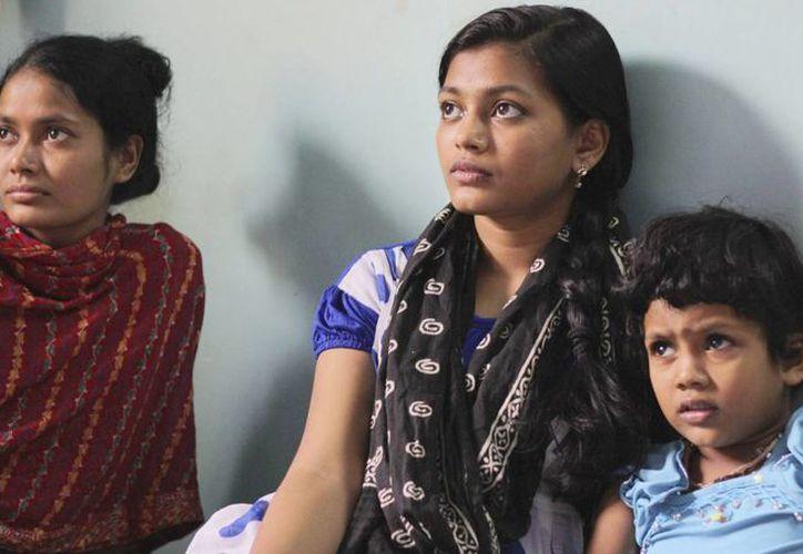 En la imagen, Rubina (c) y dos de sus hermanas viendo la televisión en su nuevo piso en Bombay. (EFE)