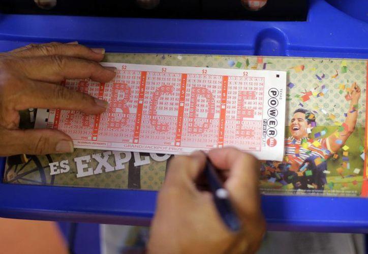 Una persona llena una boleta de la lotería Powerball. (Agencias)