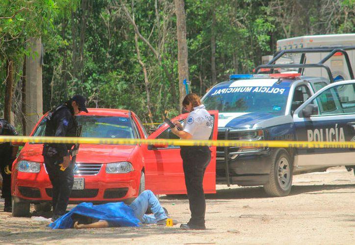 Los cadáveres quedaron tirados junto al vehículo en el que intentaron escapar. (Redacción/SIPSE)