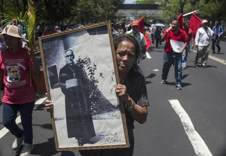 Una mujer carga un retrato de monseñor Oscar Arnulfo Romero durante una procesión el 24 de marzo del 2015 en San Salvador. (Agencias)