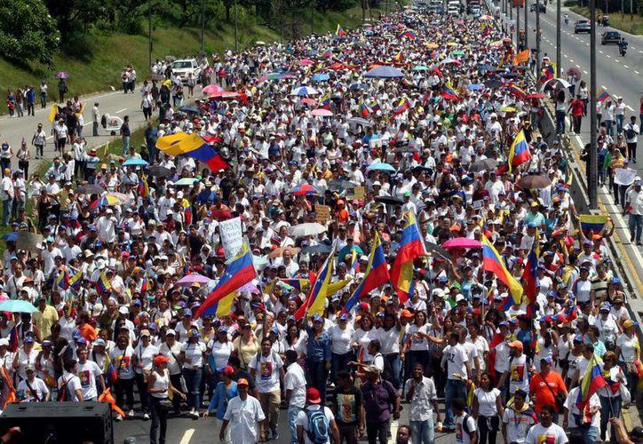 Miles de mujeres en Caracas durante la marcha en repudio por la decisión de suspender la recolección de firmas que llevarían a un referéndum contra el presidente Nicolás Maduro. (Notimex)