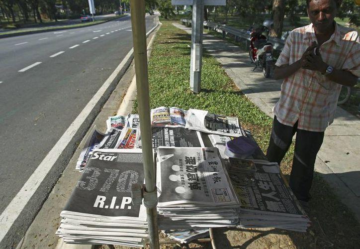 Un vendedor se encuentra junto a los periódicos que llevan los titulares de los desaparecidos Malaysia Airlines, vuelo MH370, mientras espera para los clientes en las afueras de Kuala Lumpur, Malasia. (Agencias)