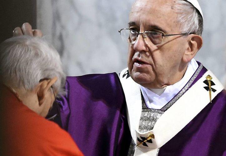 El Papa Francisco impone a una pesona la ceniza ayer miércoles en el inicio de la Cuaresma, ayer en el Vaticano. (Agencias)