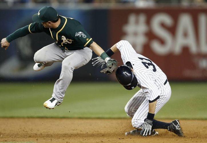 Nick Punto (1), segunda base de Oakland, fildea después de que el yanqui  Ichiro Suzuki (31) se robó la segunda base en Nueva York. (Foto: AP)