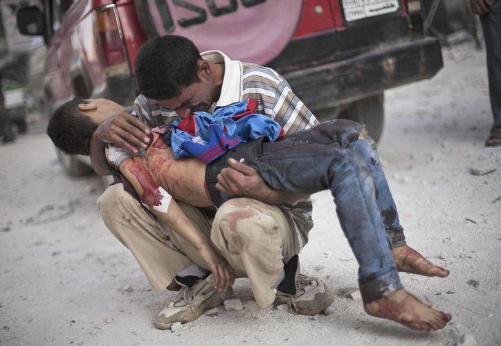 Un hombre llora mientras sostiene el cuerpo de su hijo, muerto por el ejército sirio. (Agencias)