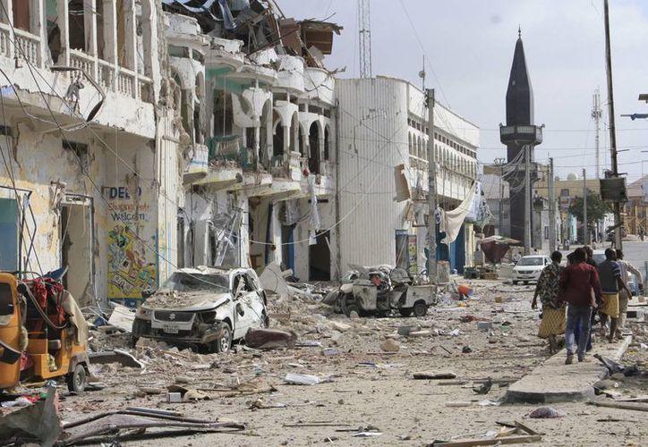 Un grupo de somalíes pasa junto a un hotel y autos destrozados por un grupo de extremistas islámicos somalíes, que entraron por la fuerza al lugar. (AP/Farah Abdi Warsameh)