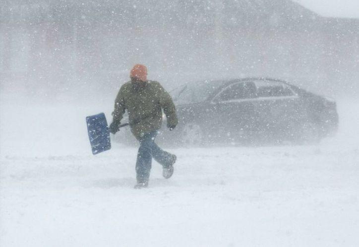 Un hombre avanza con una pala de nieve en Market Street en Illinois. No sólo las bajas temperaturas afectan a la población sino el enorme acumulamiento de nieve. (Agencias)