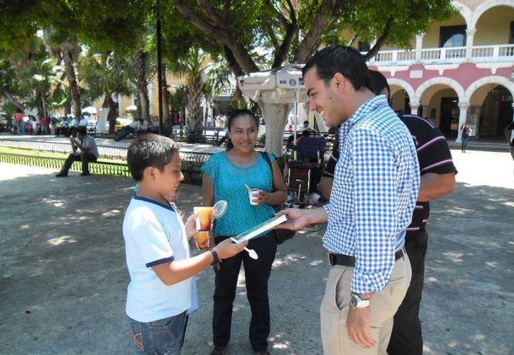 El regidor Elías Lixa Abimerhi, de la Comisión de Cultura del Cabildo de Mérida, reparte libros en la Plaza Grande. (SIPSE)