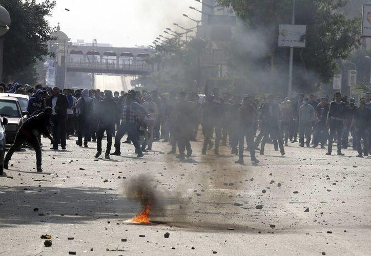 Varios seguidores de los Hermanos Musulmanes queman objetos durante las protestas islamistas, en las que intervienen fuerzas policiales antidisturbios egipcias cerca de la Universidad de El Cairo. (EFE)