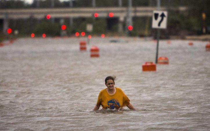 Una mujer que solo se identificó como Valerie camina por una calle inundada tras el paso del huracán Matthew luego de haber salido de un campamento para indigentes, en Savannah, Georgia. (AP/Stephen B. Morton)