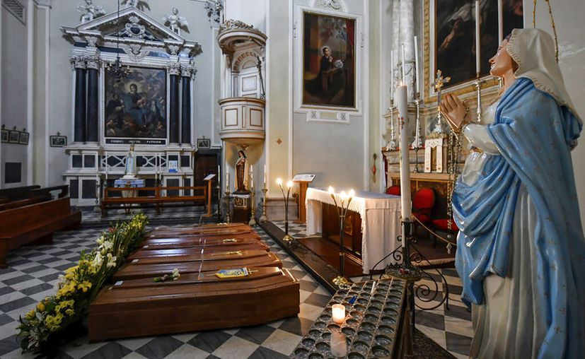 Féretros aguardan transporte al cementerio desde la iglesia de Serina, cerca de Bergamo, Italia. (Claudio Furlan/LaPresse via AP)