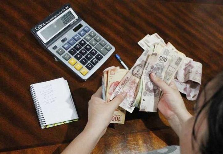 'Los trabajadores del sector industrial de Yucatán no observarán cambios en sus quincenas ante la homologación de los salarios mínimos, pues las retribuciones en ese sector están basados por encima de éstos', dijo  Mario Can Marín. Imagen de una mujer contando dinero. (Milenio Novedades)