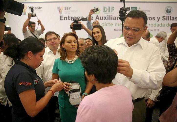 El gobernador Rolando Zapata coloca aparatos auditivios a una beneficiaria durante la sexta jornada del programa 'Para oírte mejor'. (Foto cortesía del Gobierno de Yucatán)