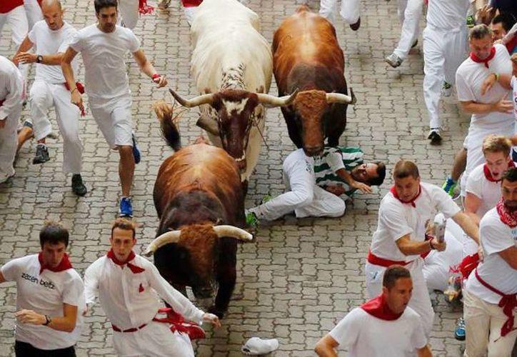Un hombre cae al suelo mientras otros siguen corriendo junto a los toros de la ganadería Jandilla, en el primer encierro de las fiestas de San Fermín, en Pamplona, España, este martes 7 de julio de 2015. (AP Foto/Daniel Ochoa de Olza)