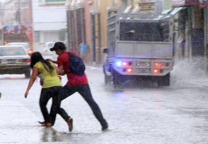 Dos transeúntes corren para ponerse a salvo de la lluvia que cayó ayer en Mérida. (SIPSE)