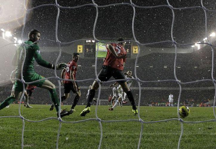 El norteamericano Clint Dempsey fue el héroe del partido al anotar (semioculto al centro) en el último minuto al Manchester United. (Agencias)