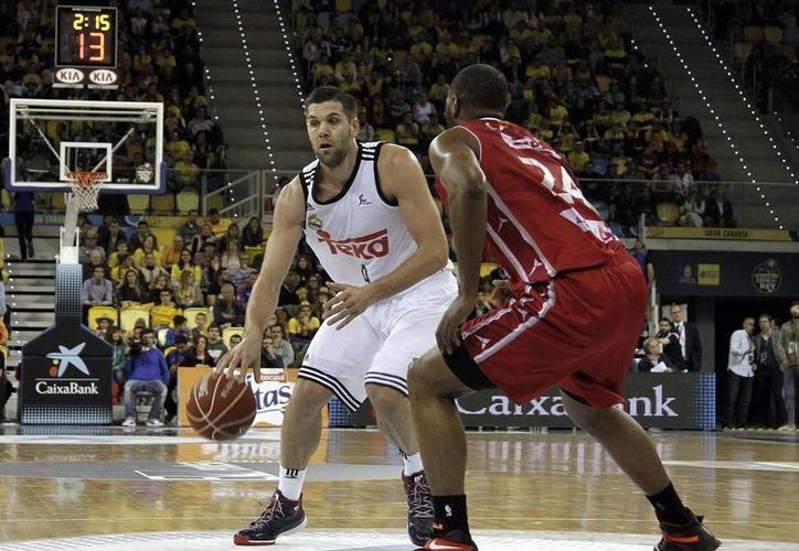 El ala pivot del Real Madrid, Felipe Reyes (i), intenta superar al alero estadounidense del CAI Zaragoza Marcus Landry, en el partido de cuartos de final de la Copa del Rey de baloncesto en el Gran Canaria Arena. (EFE)