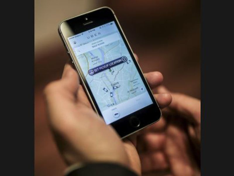 An Uber employee shows the mobile application at the official launch of the car-hailing service, in Cairo, Egypt.