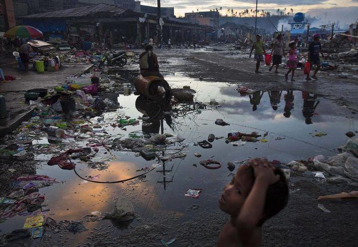 Sobrevivientes del tifón Haiyan caminan por las ruinas en las calles de Tacloban. (Agencias)