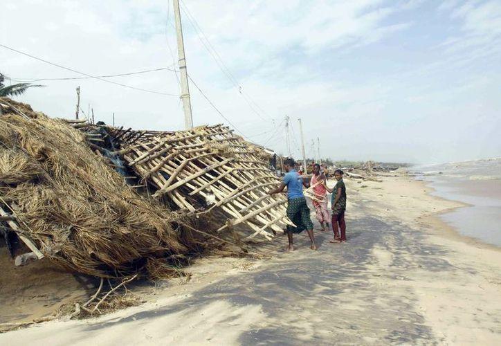 Un grupo de habitantes trata de reparar los daños causados por el ciclón Phailin en el area de Ganjam, en India. (EFE)