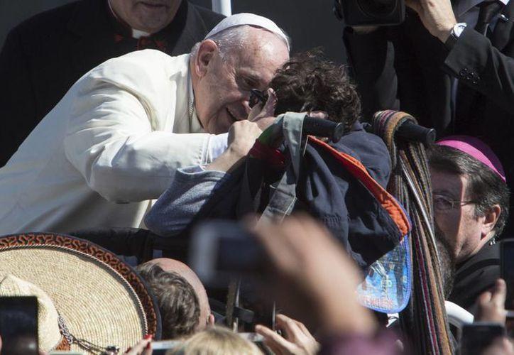Papa Francisco besa a un niño en una silla de ruedas, en el Zócalo de la Ciudad de México. (Agencias)