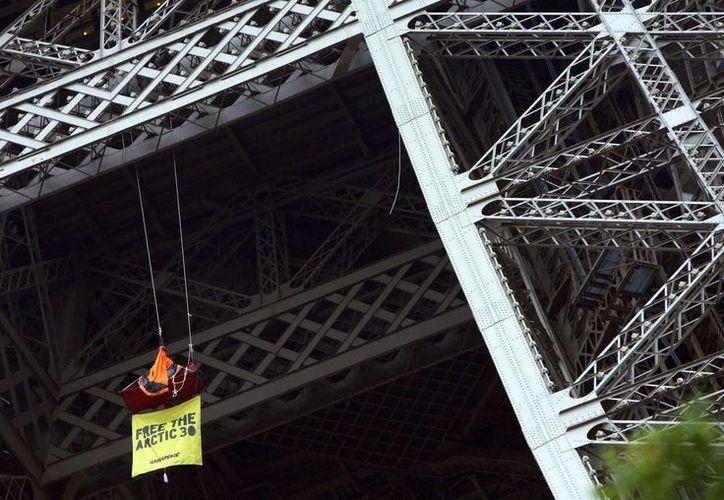 Una integrante de Greenpeace coloca una manta de protesta para pedir la liberación de 28 activistas y dos periodistas. (EFE)