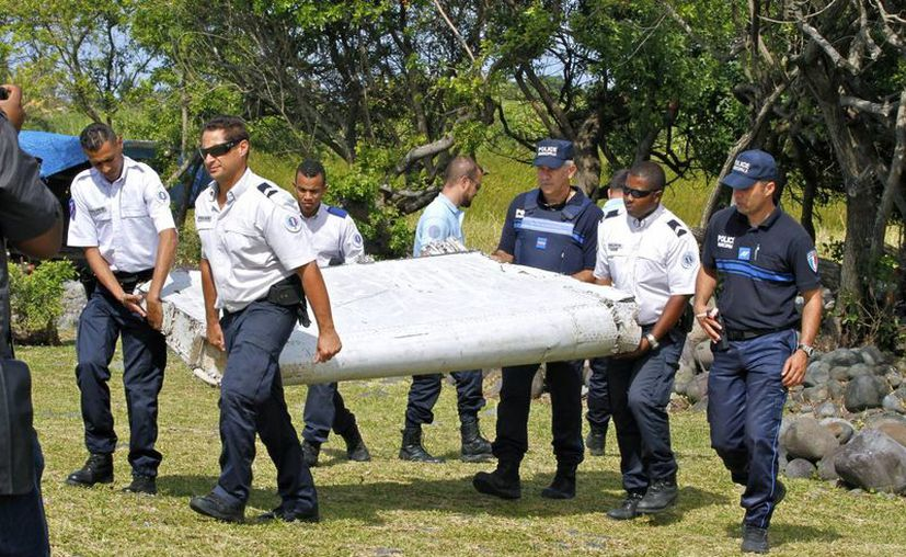 """Agentes de policía franceses llevan un pedazo de escombros de un avión en Saint- Andre, Reunión. Investigadores de seguridad de aire identificaron el componente como un """"flaperón"""" del ala Boeing 777 de Maylasia Airlines. (AP Photo/Lucas Marie)"""