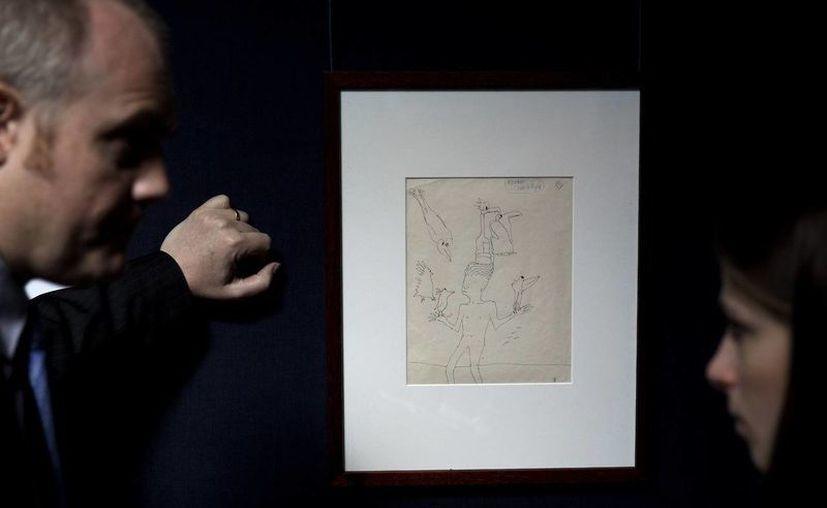 Un empleado de la casa de subastas Sotheby's habla con una periodista frente a un dibujo de un muchacho con seis aves realizado por el exBeatle John Lennon en Londres. (Agencias)