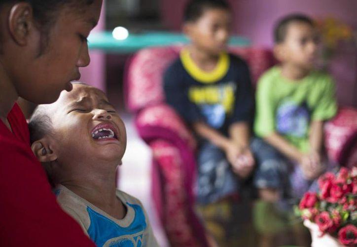 Shylyny Therese Negru, de 15 años, abraza a su hermanito de 3, Rainier Aaron. Los niños son algunos de los miles que perdieron a sus padres en el Tifón Haiyan en Filipinas. (Agencias)