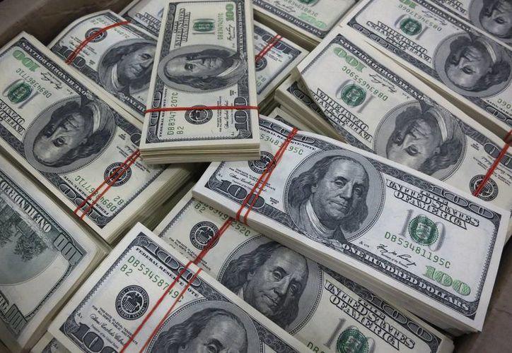 Los cárteles del narcotráfico reciben cientos de miles de dólares en ganancias, que luego convierte en pesos en transacciones aparentemente legales. (Archivo/AP)