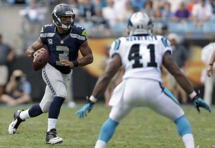 El quarterback de los Seahawks de Seattle Russell Wilson (3) avanza con el balón frente al cornerback de los Panthers de Carolina, Captain Munnerlyn, en el partido de este domingo. (Agencias)