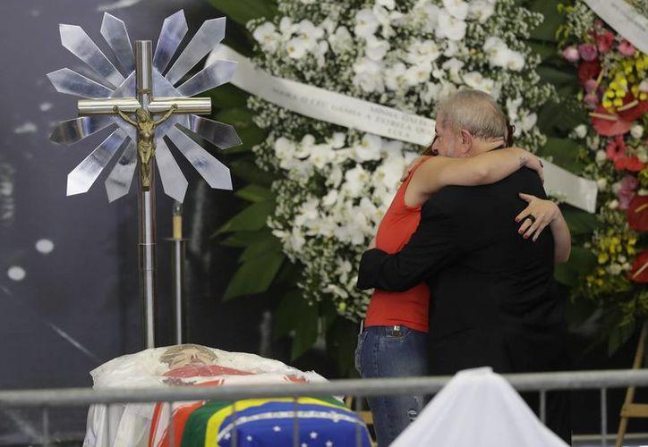 El expresidente de Brasil, Luiz Inácio Lula da Silva, recibe un abrazo de un simpatizante junto al cuerpo de su esposa Marisa Leticia Lula da Silva, durante su funeral. (AP/Andre Penner)