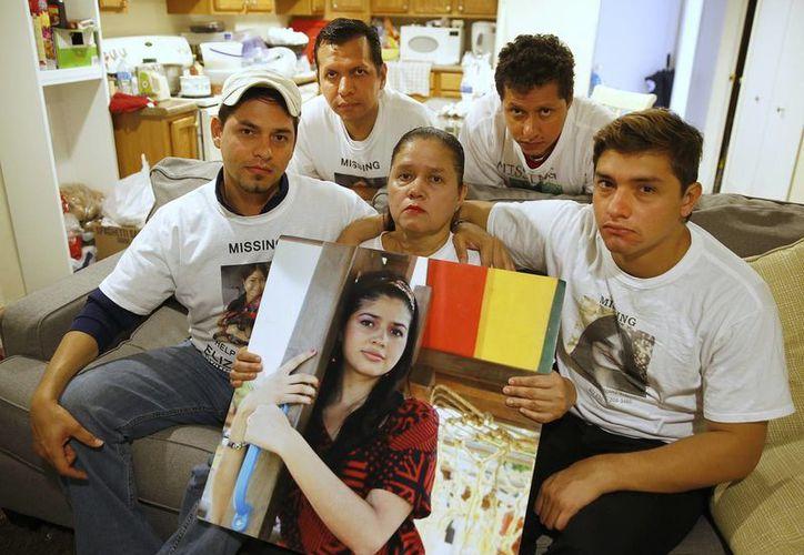 Libertad Salgado Figueroa (c), madre de la joven desaparecida Elizabeth Laguna Salgado, sostiene un poster de su hija junto a sus hijos y hermanos en la ciudad de Orem, Utah. (EFE)
