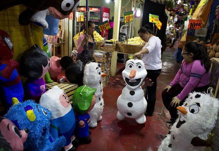 """Jasmín Membrillo y su hija eligen una piñata de Olaf, personaje de la cinta de Disney """"Frozen: Una aventura congelada"""", en el mercado La Merced en la Ciudad de México. (Agencias)"""