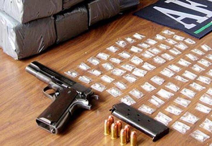 Al detenido junto con una mujer se les aseguró un fusil, una pistola, dos cargadores, 39 cartuchos útiles y una bolsa con un kilo 200 gramos de marihuana. (Archivo Sipse)