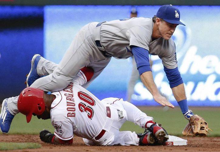 El segunda base de Dodgers, Chase Utley (arriba) choca con Jason Bourgeois, de Cincinnati, después de lanzar a primera base para conseguir un doble play en el primer inning del partido ganado 5-1 por Dodgers. (Foto: AP)