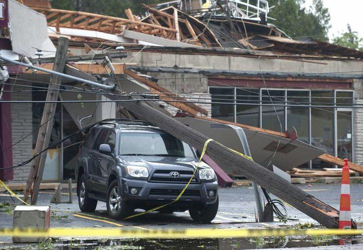 La foto muestra los daños causados a un centro comercial y un vehículo por el paso de un tornado por Gran Rapids, Michigan. (Agencias)