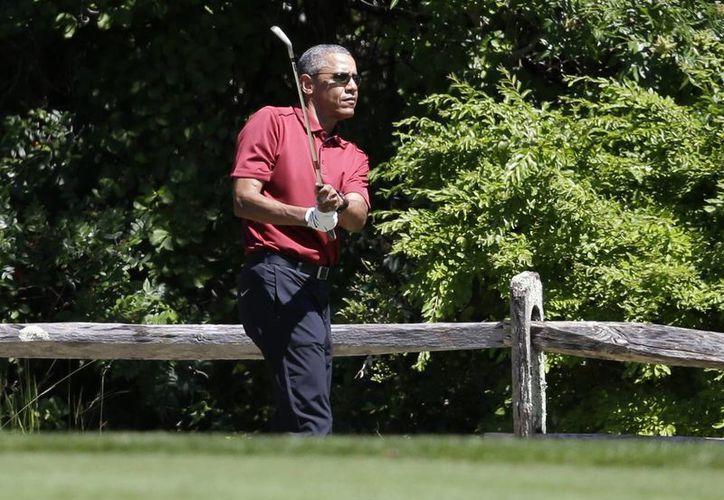 El presidente Barack Obama sonríe mientras juega golf en Oak Bluffs, Massachusetts, mientras estaba de vacaciones. (AP)